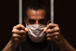 Man with white medical mask standing in the dark, holding bars with his bare hands, locked away in dark, in isolation and quarantine