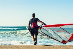 Man with windsurf board on seascape background with sea and clouds. Summer concept