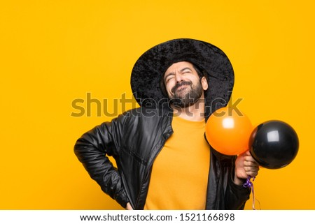 Man with witch hat holding black and orange air balloons for halloween party suffering from backache for having made an effort