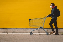 Man with with a shopping cart in front of a store, wearing a mask during a coronavirus pandemic / Covid-19.