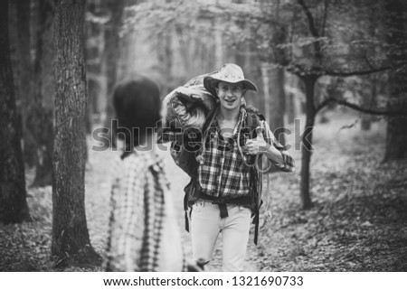 Man with woman hiking with overnight stay or picnic. Couple in love hiking in forest with touristic equipment, trees on background, defocused. Young couple with happy faces walks. Tourists concept.