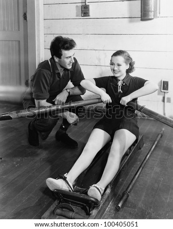 Man with woman using rowing machine