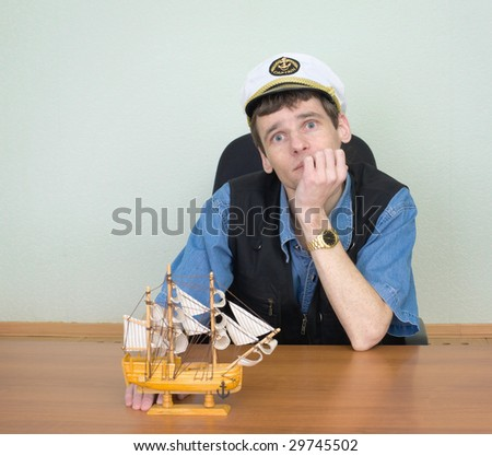 Man with wooden model of a sailing vessel