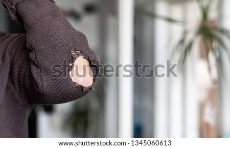 Man with worn to holes fabric sweater with pipped sleeve - Person wearing rubbed old shirt with hole on sleeve - Ragged cloth hole elbow sleeve