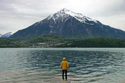 Man with yellow rain jacket in front of huge snow-covered mountain in Switzerland. Mount Niesen with green trees and water of lake Thun.