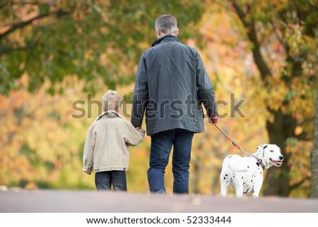 Man With Young Son Walking Dog Through Autumn Park - stock photo