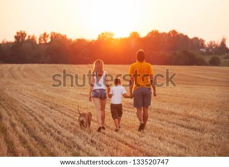 man, woman and dog walking on sunset