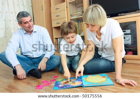 man, woman and little boy sitting on the floor in living room and reading book
