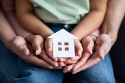Man, woman and little child holding cutout paper house figure in hands, conceptual image for family housing, home mortgage, real estate, insurance or adoption, closeup shot