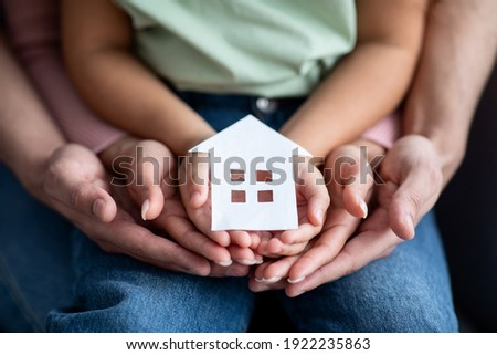 Man, woman and little child holding cutout paper house figure in hands, conceptual image for family housing, home mortgage, real estate, insurance or adoption, closeup shot Foto stock ©