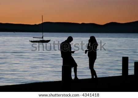 Man, woman and small sailboat at lake with beautiful sunset.