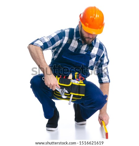 Man worker builder with helmet and tool belt, building level on white background isolation #1516621619