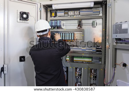 Man worker checking advanced industrial control panel #430838587