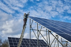 Man worker electrician repairing photovoltaic solar module, standing on a top of ladder under cloudy sky, installing solar photovoltaic panel. Concept of alternative energy sources and innovations.