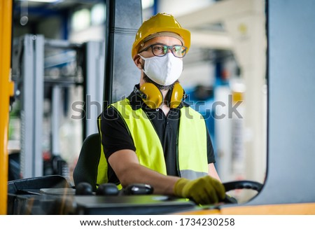 Man worker forklift driver with protective mask working in industrial factory or warehouse.