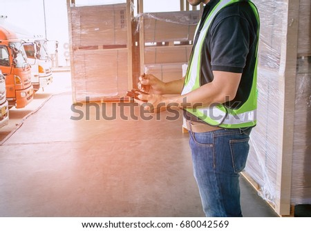 Man worker handling a Bluetooth barcode scanner with checking on screen, logistic warehouse by truck #680042569
