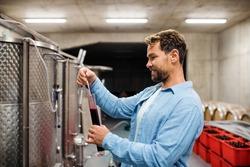 Man worker measuring gravity indoors, wine making concept.
