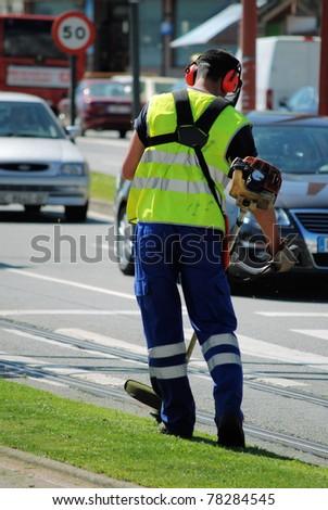 man  worker mows a grass on a city lawn