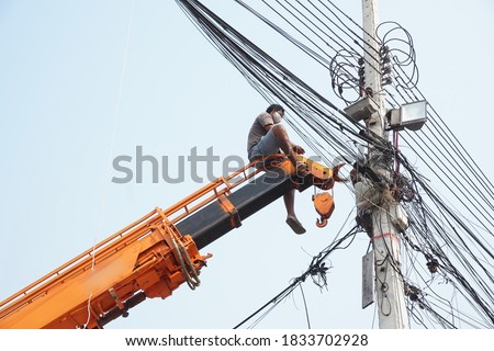 Man, worker on top of crane tractor for maintenance electric cables without safety belt is risk work. Concept of unsafe work place, risk work, unsafe work.                               Foto stock ©