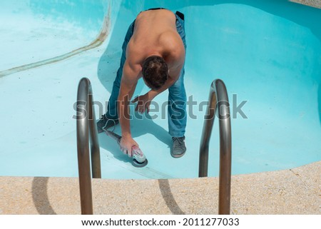 man worker repairs the inner surface, the bottom of the pool with a tool on a hot day. Preparing the pool for filling with water. Pool damage repair