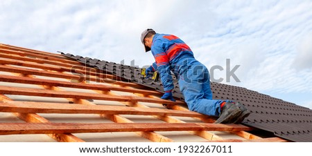 Man worker uses a power drill to attach a cap  metal roofing job with screws. Сток-фото ©