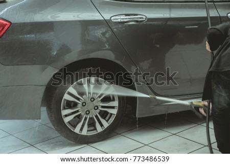 Man worker washing car by pressurized water  #773486539