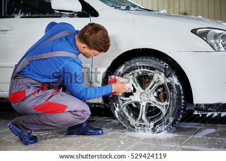 Man worker washing car's alloy rims on a car wash. #529424119