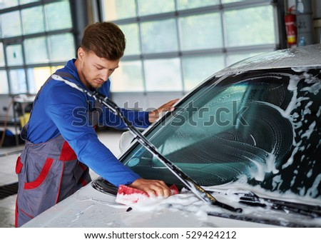 Man worker washing windshield with sponge on a car wash. #529424212