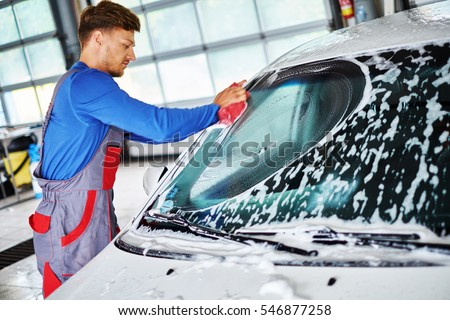 Man worker washing windshield with sponge on a car wash #546877258