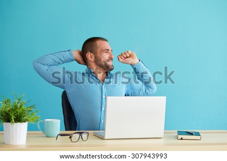 Man working at desk in office stretching his back at desk
