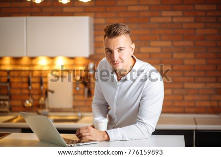 Man working at home with laptop on the kitchen desk, holding cup of coffee and looking at camera