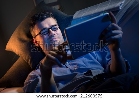 Man working at night lying down on sofa in the living room with tablet.