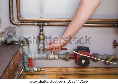 Man working at pipes. Employee's hand turning on or turning off water supply in the boiler room. Commercial plumbing company. Professional service concept.