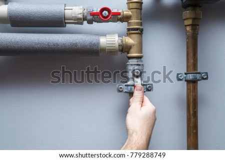 Man working at pipes. Turning on or turning off water supply in the boiler room. Plumbing concept.