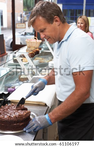 Man Working Behind Counter In Cafe Slicing Cake