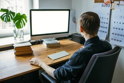 Man working from home office. Computer with blank empty screen for copy space and information. Businessman from behind shoulder view. A creative entrepreneur
