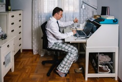 Man working from home with laptop wearing shirt, tie and pajama pants
