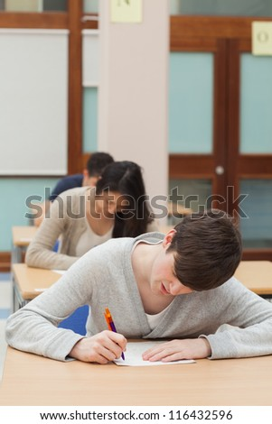 Man working hard on exam paper in exam hall