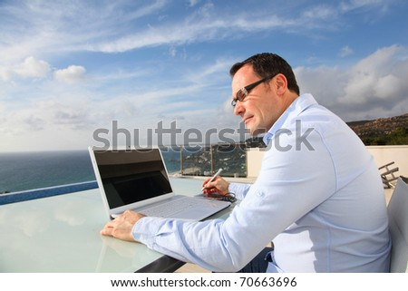 Man working in front of the sea during vacation time
