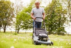 Man Working In Garden Cutting Grass With Lawn Mower