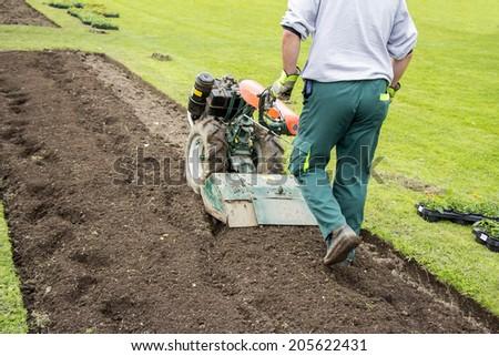 Man working in the garden with Garden Tiller  #205622431