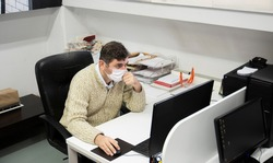Man working in the office during the pandemic period. Ways to be protected from Covid19.  With Mask.