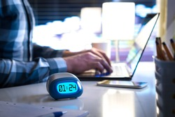 Man working late. Workaholic or being behind schedule concept. Business person in modern office building or home at night using laptop. Time in digital clock on table in workstation.