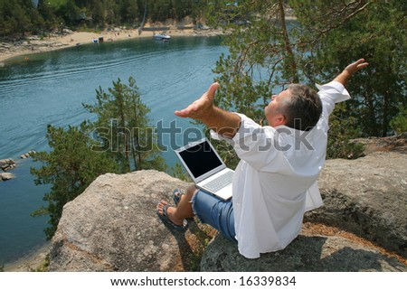 Man working on a laptop on the rocks