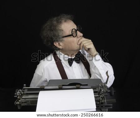 Man working on a vintage typewriter/Author Working on Typewriter/Man with glasses working on typewriter