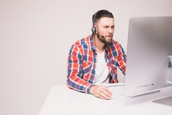 Man working on computer with headset in office