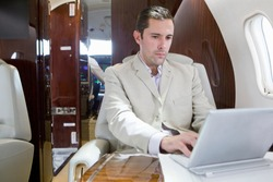 Man working on digital tablet on private jet