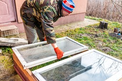 Man working on diy project construction closeup of vegetable winter garden for raised bed cold frame box in Ukraine dacha by farm house