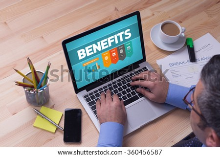 Man working on laptop with BENEFITS on a screen