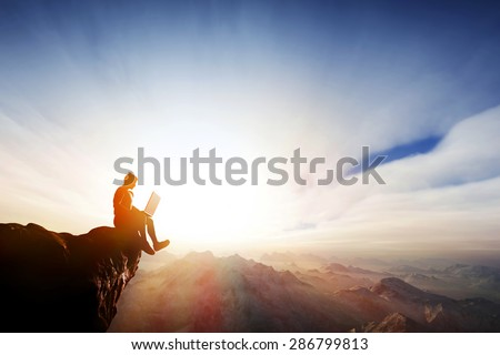 Man working on notebook sitting on cliff on top of the mountains. Concepts of staying online everywhere, internet, freedom reception etc.